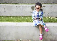 Teléfono elegante del juego asiático del niño en parque del jardín Foto de archivo libre de regalías