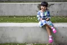 Teléfono elegante del juego asiático del niño en parque del jardín Imagen de archivo libre de regalías