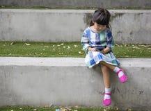 Teléfono elegante del juego asiático del niño en parque del jardín Fotografía de archivo libre de regalías