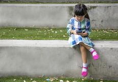 Teléfono elegante del juego asiático del niño en parque del jardín Imagenes de archivo