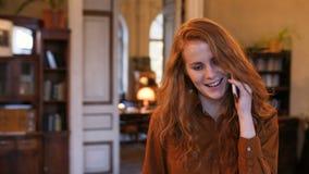 Teléfono elegante del teléfono móvil de la mujer caucásica roja joven del pelo que manda un SMS que camina en café almacen de video