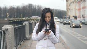 Teléfono elegante del teléfono móvil de la mujer que manda un SMS que camina asiática joven en ciudad metrajes