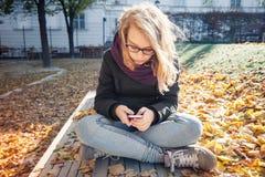 Teléfono elegante del usin rubio lindo del adolescente Imágenes de archivo libres de regalías