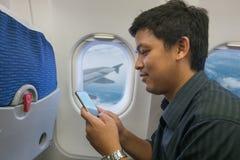 Teléfono elegante del uso del hombre en aeroplano Fotografía de archivo libre de regalías