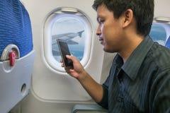 Teléfono elegante del uso del hombre en aeroplano Fotos de archivo