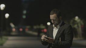Teléfono elegante descontentado del uso barbudo del hombre de negocios, mientras que se coloca en la calle de la ciudad, mensajes Fotos de archivo