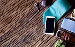 Teléfono elegante en blanco de Moblie con el accessorie del teléfono y del caballero del oído Foto de archivo