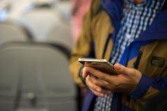 Teléfono elegante en la mano del hombre en el aeroplano Foco suave foto de archivo