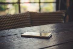 Teléfono elegante en la tabla de madera con el fondo de la falta de definición Imágenes de archivo libres de regalías