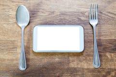 Teléfono elegante en la tabla y la cuchara de madera de la bifurcación con la trayectoria de recortes o Foto de archivo libre de regalías