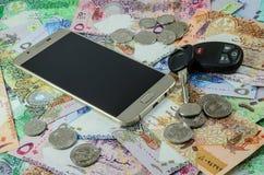 Teléfono elegante, llave del coche y moneda de Qatar Imagen de archivo
