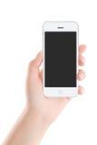 Teléfono elegante móvil blanco con la pantalla en blanco en mano femenina Foto de archivo libre de regalías