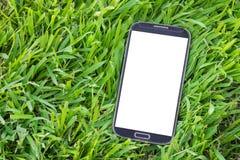 Teléfono elegante negro con la pantalla aislada en hierba Fotos de archivo
