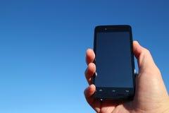 Teléfono elegante negro y la mano en el cielo azul Imagenes de archivo