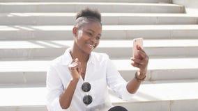 Teléfono elegante que se considera femenino del blogger afroamericano elegante hermoso de Internet almacen de metraje de vídeo
