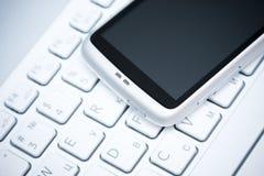 Teléfono elegante sobre el teclado blanco Imagen de archivo libre de regalías