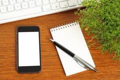 Teléfono elegante, teclado, libreta, pluma y planta verde Imágenes de archivo libres de regalías