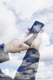 Teléfono elegante y la nube Foto de archivo libre de regalías