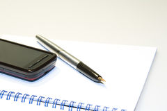 Teléfono en el cuaderno foto de archivo