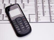 Teléfono en el teclado de la computadora portátil Imagenes de archivo