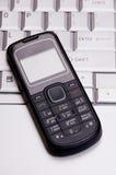 Teléfono en el teclado de la computadora portátil Imagen de archivo