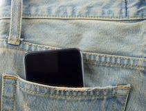 Teléfono en un bolsillo trasero de vaqueros del dril de algodón como fondo Imágenes de archivo libres de regalías