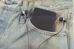 Teléfono en un bolsillo trasero de vaqueros del dril de algodón como fondo Fotos de archivo libres de regalías
