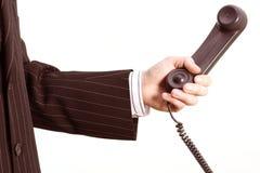 Teléfono en una mano del negocio foto de archivo