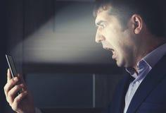 Teléfono enojado de la mano del hombre foto de archivo libre de regalías