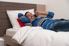 Teléfono feliz de In Bedroom On del estudiante masculino Imagen de archivo