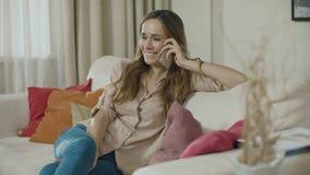 Teléfono feliz de la llamada de la mujer en el sofá en casa Mujer sonriente que habla el tel?fono m?vil metrajes