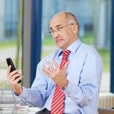 Teléfono frustrado de Looking At Cordless del hombre de negocios imagen de archivo