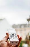 Teléfono inalámbrico que hace frente a la ventana Fotos de archivo