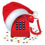 Teléfono inmóvil rojo de la Navidad con el telclado numérico del botón en el casquillo de Santa Claus Fotos de archivo libres de regalías