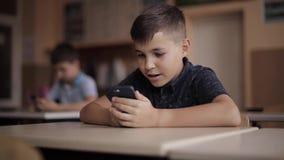 Teléfono lindo del uso del niño pequeño durante la lección Dos schollboy en clase almacen de metraje de vídeo