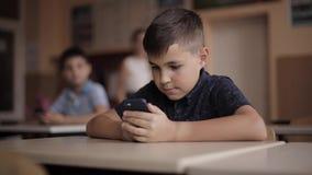 Teléfono lindo del uso del niño pequeño durante la lección Dos schollboy en clase almacen de video