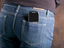 Teléfono móvil abstracto en el bolsillo trasero de vaqueros Imagen de archivo libre de regalías