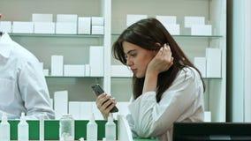 Teléfono móvil agujereado del uso femenino del farmacéutico en la farmacia metrajes