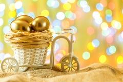 Teléfono móvil amarillo Huevos de oro en un carro de la bicicleta Huevo Pascua feliz Imagen de archivo