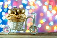 Teléfono móvil amarillo Huevos de oro en un carro de la bicicleta Huevo Pascua feliz Fotografía de archivo libre de regalías