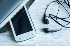Teléfono móvil, auriculares en la mesa de madera de la oficina Fotos de archivo