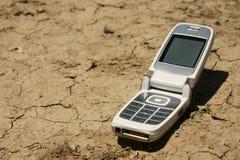 Teléfono móvil blanco en una cama de río seca Imagenes de archivo