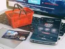 Teléfono móvil, cesta de compras y tarjeta de crédito en el teclado del ordenador portátil ilustración del vector