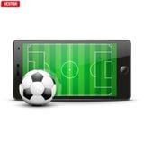 Teléfono móvil con el balón de fútbol y campo en Imágenes de archivo libres de regalías
