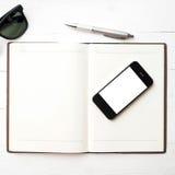 Teléfono móvil con el cuaderno y las gafas de sol Imagen de archivo