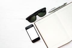 Teléfono móvil con el cuaderno y las gafas de sol Fotografía de archivo libre de regalías