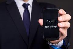 Teléfono móvil con el nuevo mensaje en mano del hombre de negocios Foto de archivo