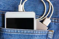 Teléfono móvil con la batería móvil de reserva en bolsillo de la mezclilla el teléfono móvil es poder de la transferencia de la b foto de archivo libre de regalías