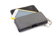 Teléfono móvil con la cubierta negra en el fondo blanco Imagen de archivo libre de regalías