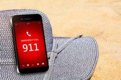 Teléfono móvil con la emergencia número 911 en la playa Foto de archivo libre de regalías